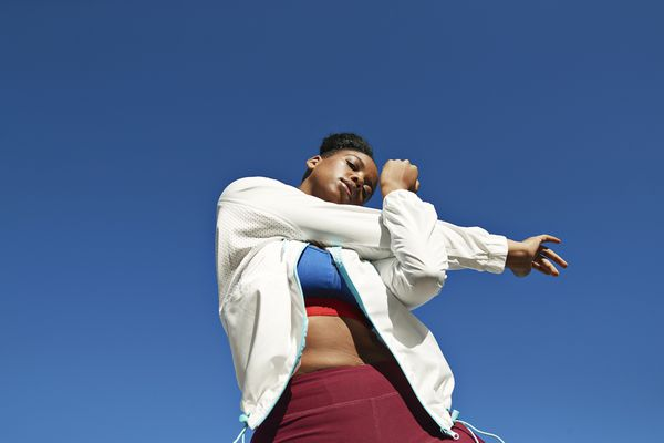 woman in white jacket stretching arms before a workout