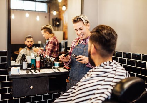 Hairdresser getting ready to cut male client's hair