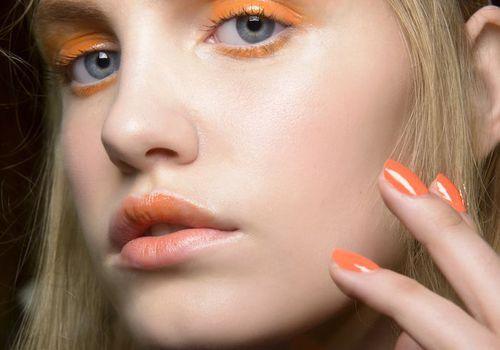 woman with orange makeup and orange nail polish