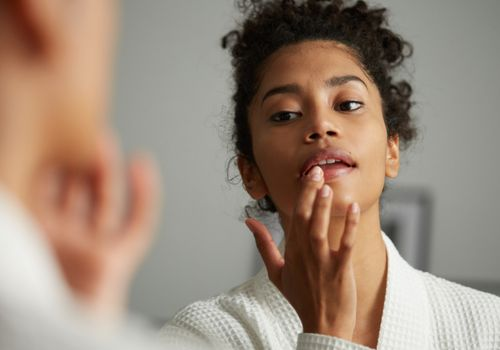 woman checking lips in mirror