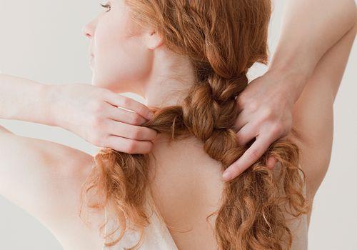 young woman braiding hair