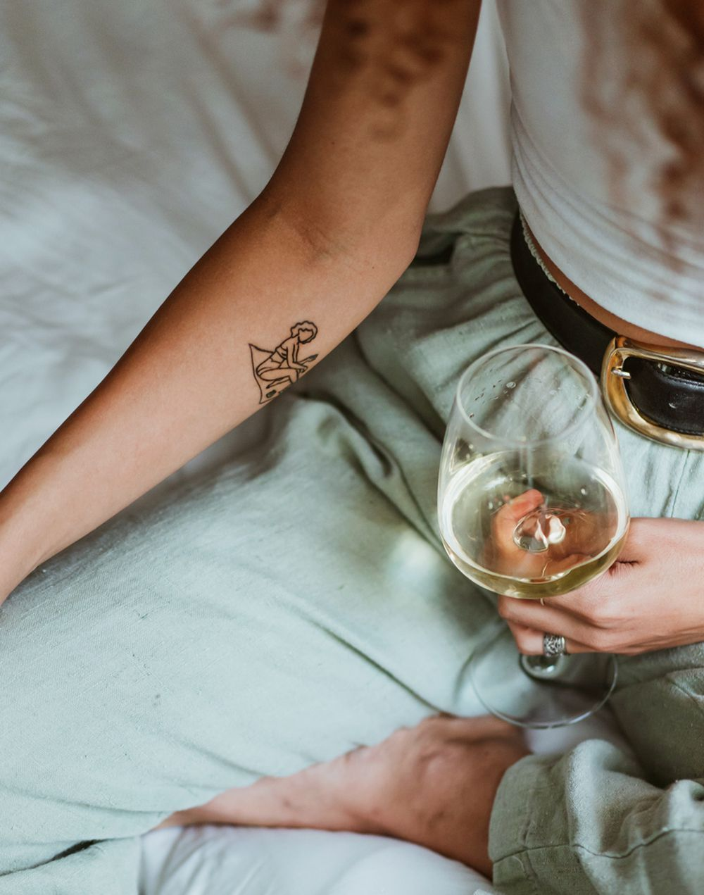 closeup of person with tattoo holding wine glass
