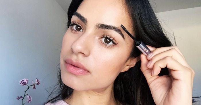 woman with thick eyebrows applying eyebrow gel