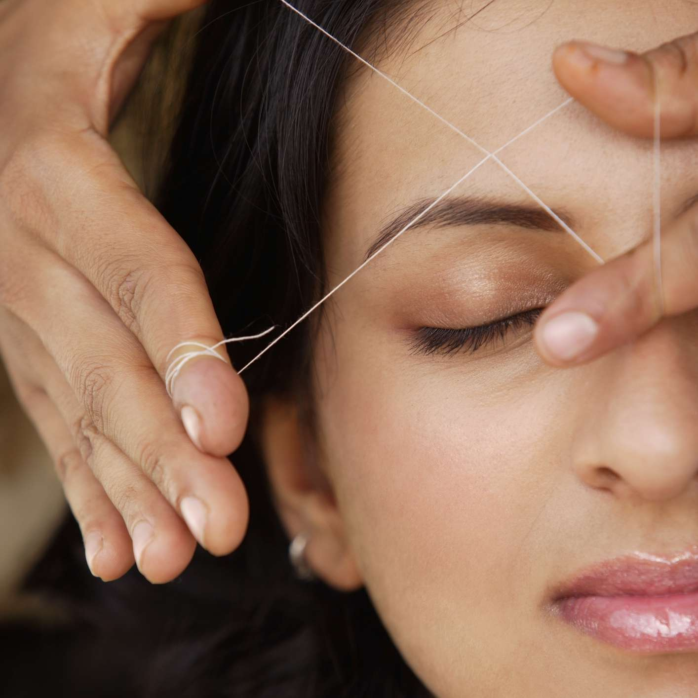 Young woman getting eyebrows threaded