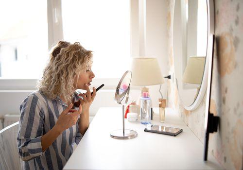 Young woman applying make up, sitting at dressing table at home