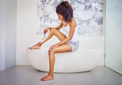 woman shaving on a bathtub