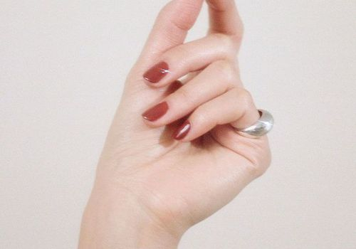 Hand with red nail polish and silver ring