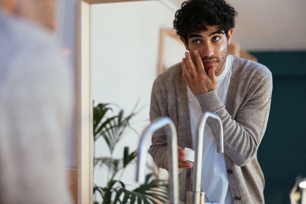 Man applying skincare in mirror