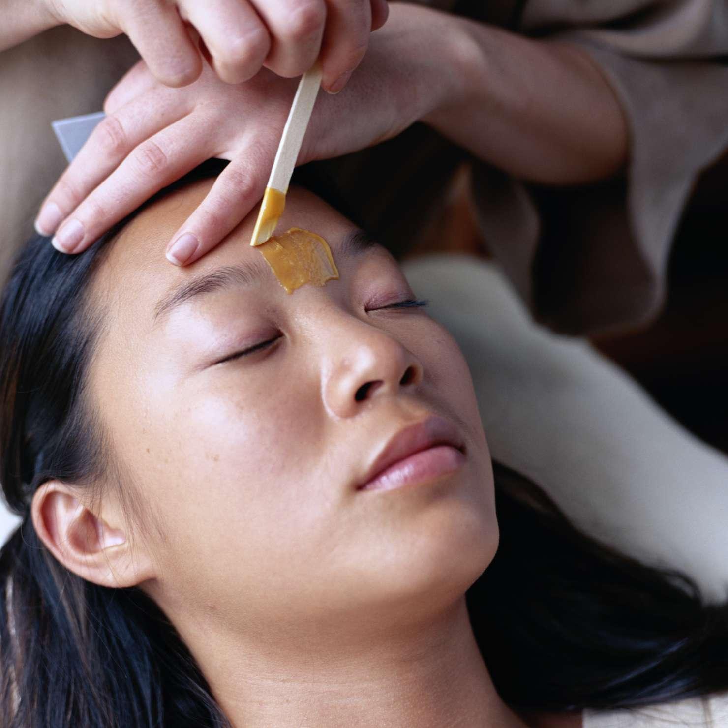 A woman having her eyebrows sugar waxed