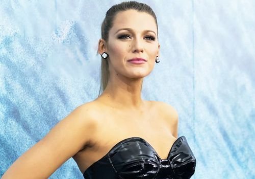 Blake Lively on red carpet in black dress with hair in ponytail