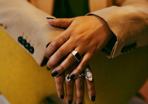 closeup of hands with rings and black nail polish