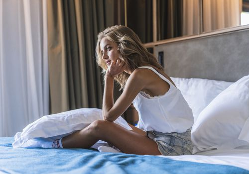 woman sitting on a bed having a bad day